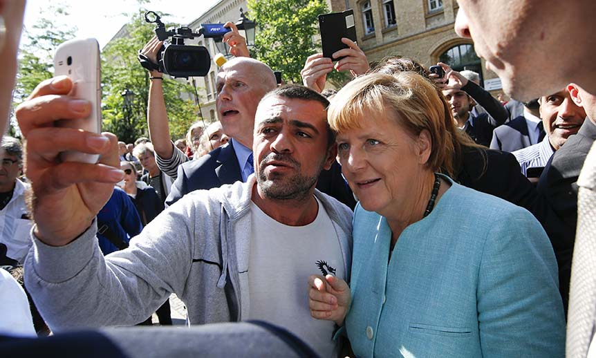 A migrant takes a selfie with German Chancellor Angela Merkel outside a refugee camp near the Federal Office for Migration and Refugees after registration at Berlin's Spandau district, Germany September 10, 2015. (Fabrizio Bensch/Reuters)